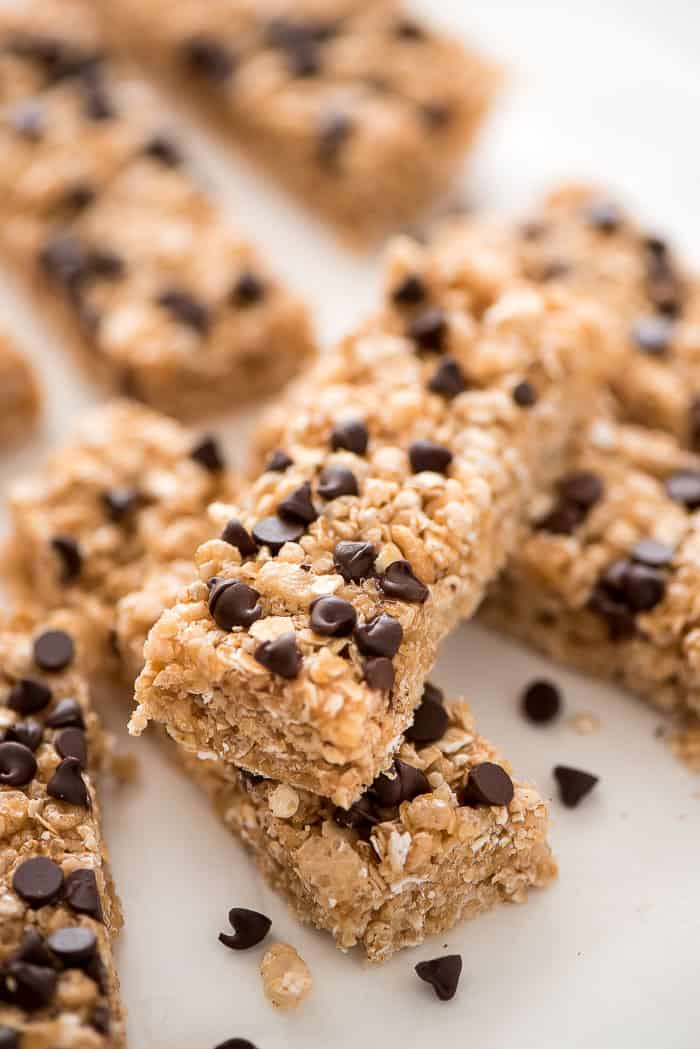 No bake chocolate chip granola bars on parchment paper with chocolate chips on the side
