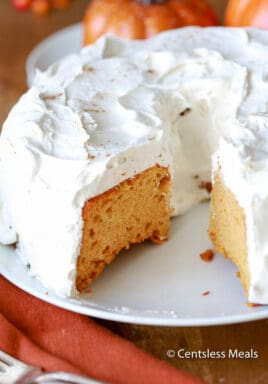 Pumpkin angel food cake on a white plate with a piece taken out