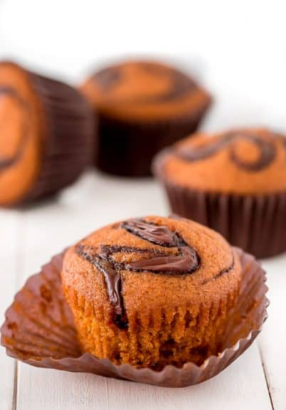 Nutella pumpkin muffins on a wooden board with one out of the wrapper