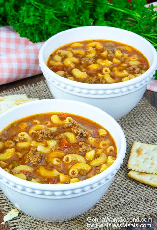 Beef and Tomato Macaroni Soup into white bowls with crackers on the side