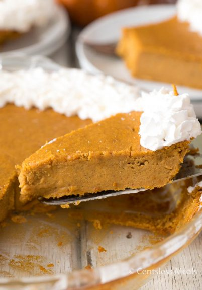 Piece of pumpkin pie on a pie server being served from the pie plate