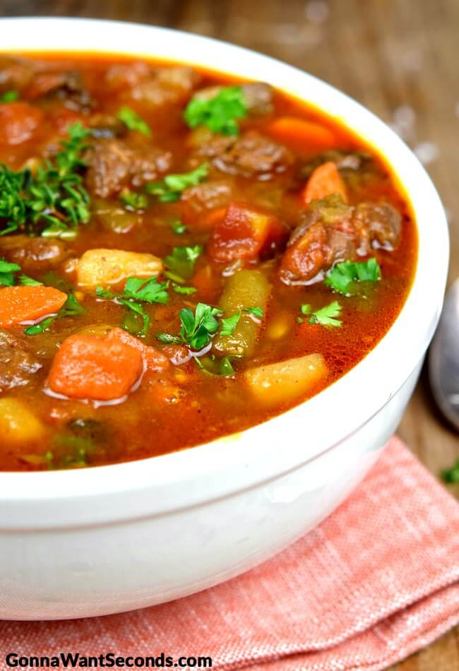 Veggie and Beef Soup in a white bowl with parsley