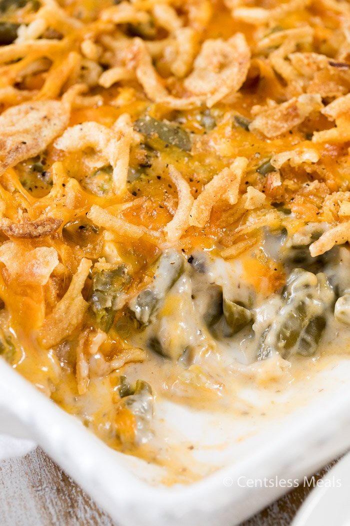 White casserole dish filled with green bean casserole with a spoonful taken out