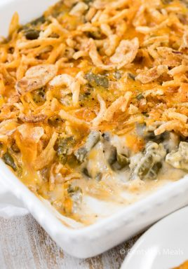 Green bean casserole in a white casserole dish with a spoonful taken out