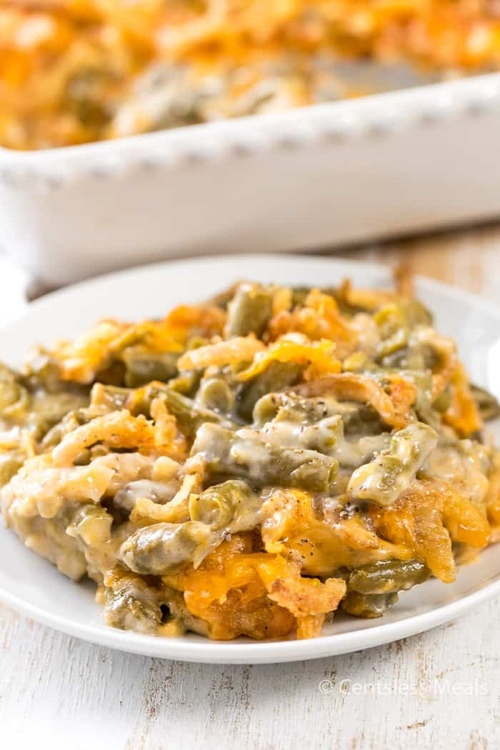 Green bean casserole on a white plate with a casserole dish in the background