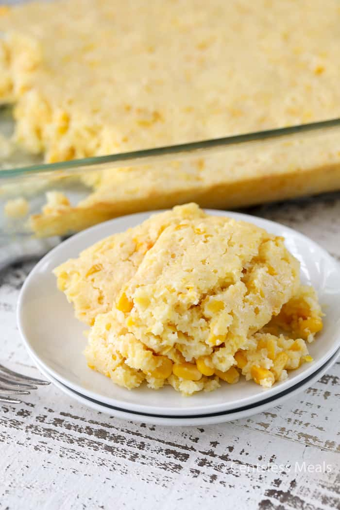 Creamed corn casserole on a white plate with the casserole dish on the side