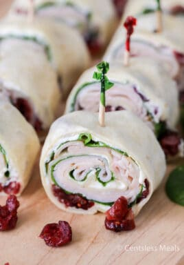 Cranberry turkey pinwheels on a wooden board with cranberries on the side