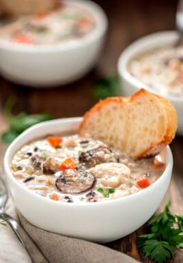 Slow cooker chicken wild rice soup in a white bowl with a slice of bread and a spoon on the side