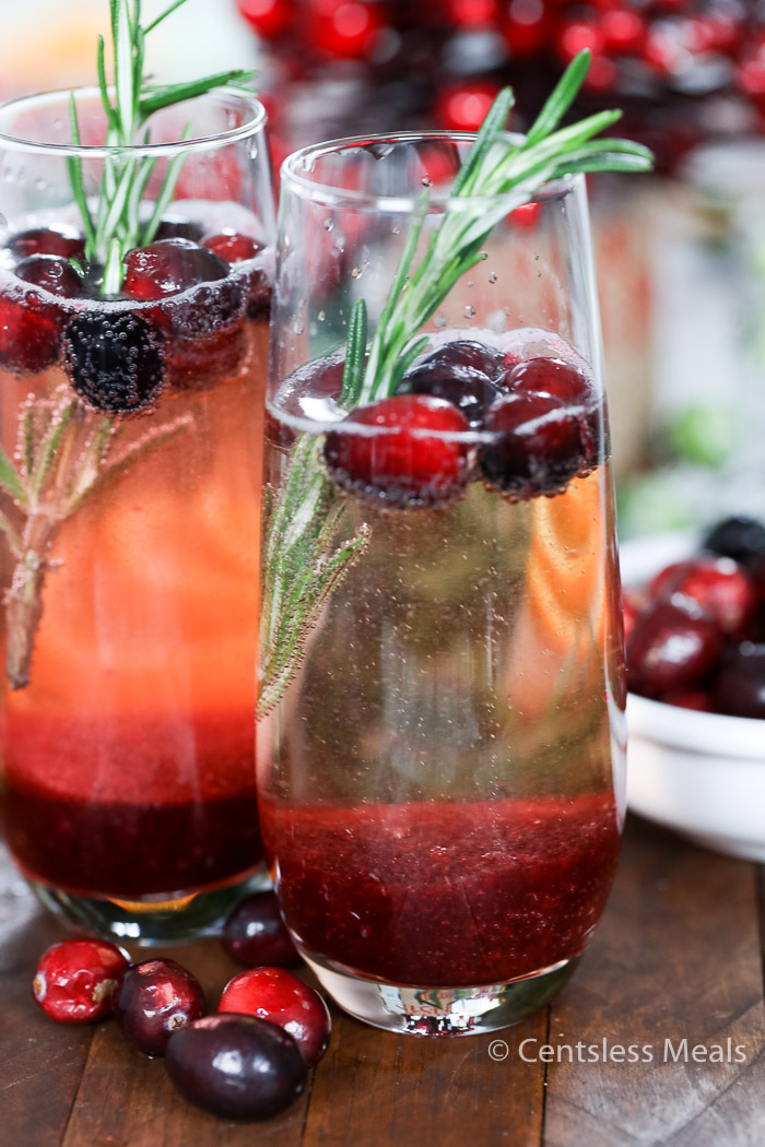 Cranberry Mimosa is made with cranberry puree mixed with champagne, garnished with fresh cranberries and a sprig of rosemary to create a jubilant drink to accent your holiday table.