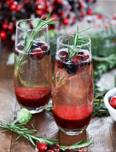 Cranberry mimosas in glasses with cranberries and rosemary as garnish