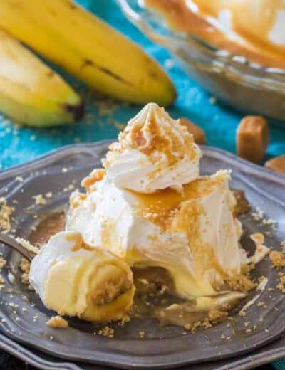 Piece of salted caramel banana cream pie on a plate with bananas in the background
