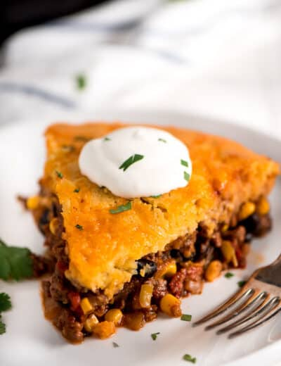 Tamale pie on a white plate with sour cream and a fork