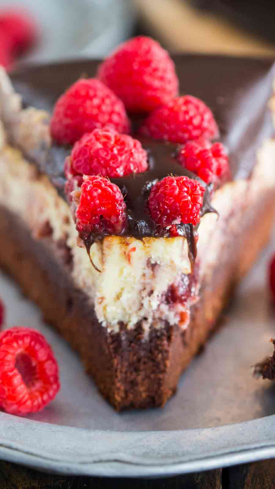 Brownie Bottom Raspberry Cheesecake is the perfect dessert when you can't decide between fruit or chocolate. A brownie bottom topped with a creamy New York style cheesecake and a hefty amount of raspberry preserves.