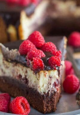 Brownie Bottom Raspberry Cheesecake is a sinful combination of chocolate and creamy raspberry cheesecake topped with chocolate ganache.