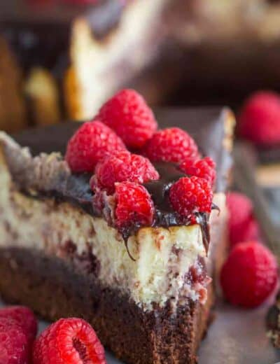 Slice of Brownie Bottom Raspberry Cheesecake on a plate with a bite taken out of it