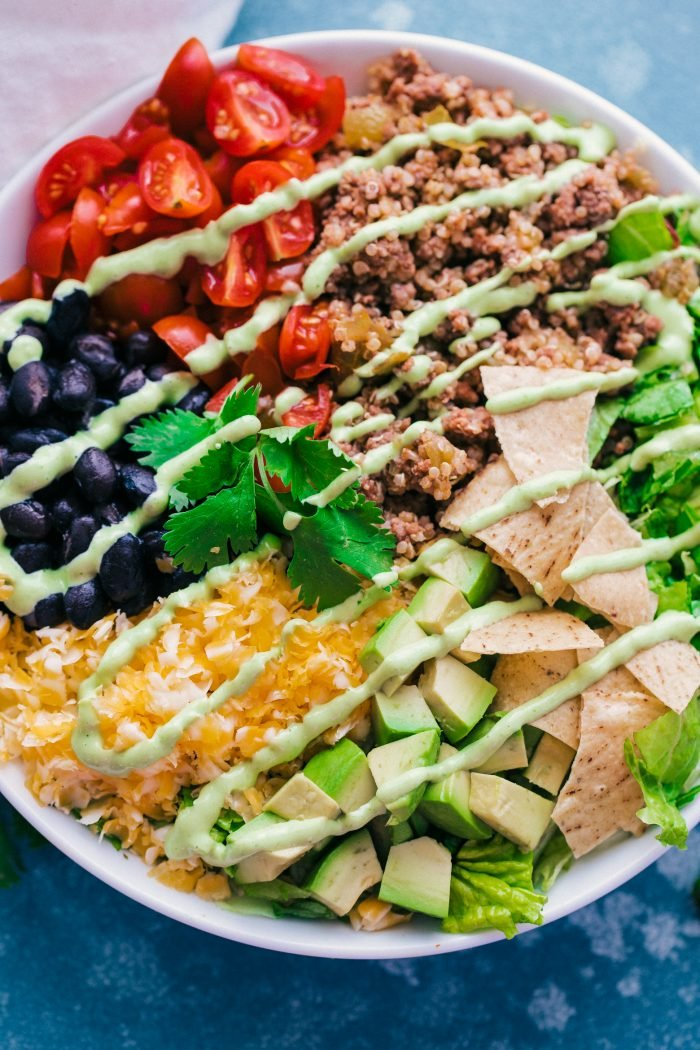 Taco Salad Bowls with Creamy Avocado Dressing are a great Taco Bar idea! Put together all your favorite taco toppings like ground beef or chicken, quinoa, cheese, olives, black beans, avocados, hot sauce, tomatoes, and chips. Your family and guests will love it!