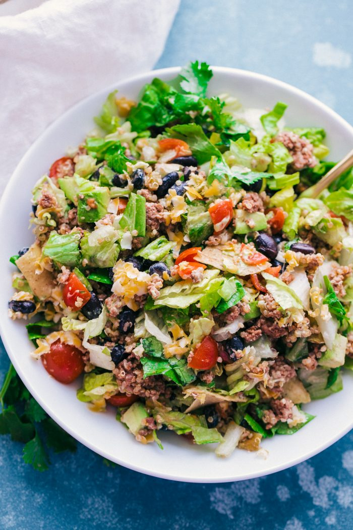 Taco Salad Bowls with Creamy Avocado Dressing are loaded with spicy ground beef, lettuce, tomatoes, green chilis, cheese, avocado, tortilla chips and quinoa, all topped with a delicious Creamy Avocado Dressing. They are the perfect way to enjoy a taco and salad all in one!
