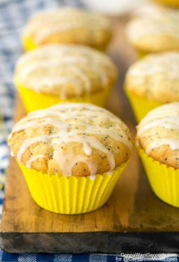 Glazed Lemon Poppy Seed Muffins on a wooden board.