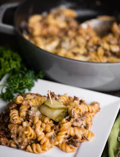 Cheeseburger pasta casserole on a white plate with a pickle on top