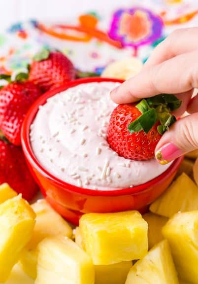 Strawberry fruit dip with a strawberry being dipped in