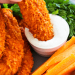 Baked buffalo chicken tenders being dipped in dip