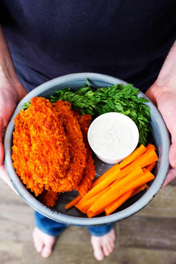 Baked Buffalo Chicken Tenders served with carrot sticks, ranch dressing and garnished with parsley