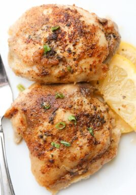 Baked lemon butter chicken thighs on a plate with green onions