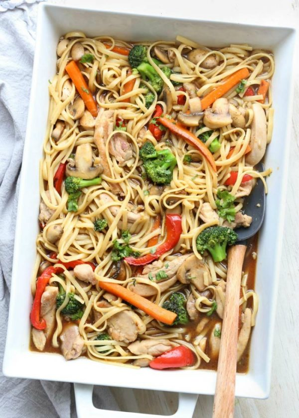 Chicken vegetable and pasta stir fry in a casserole dish with a spoon