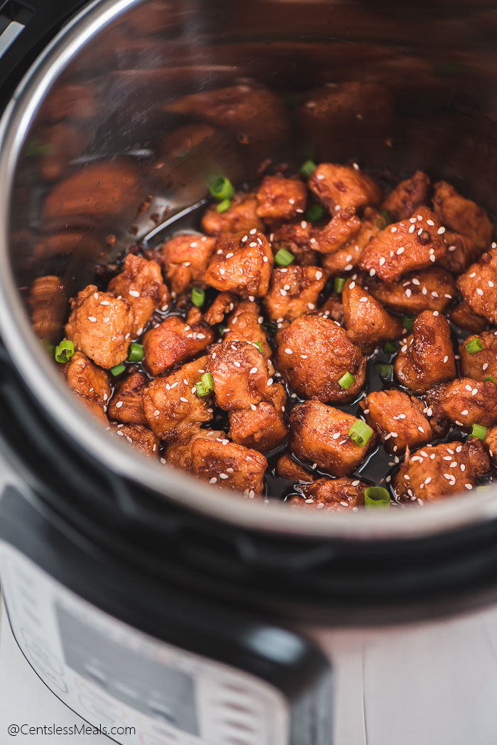 Honey Garlic Chicken sprinkled with green onions and sesame seeds in an Instant Pot.