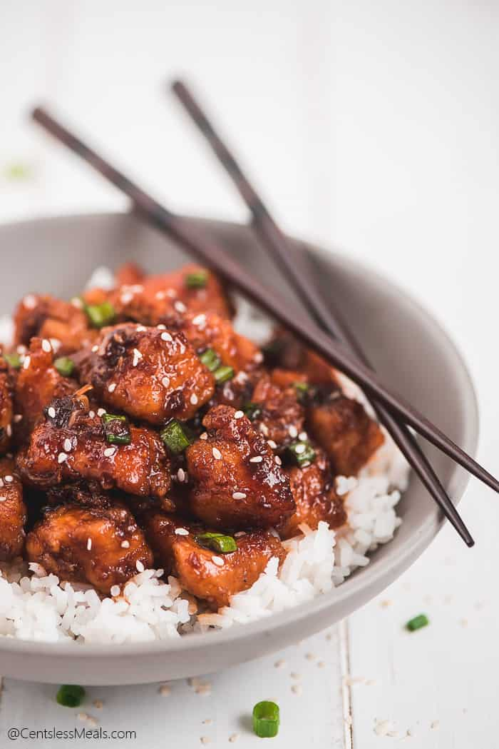 Instant Pot Honey Garlic Chicken on top of rice in a bowl, sprinkled with green onions, sesame seeds, and chops sticks resting on the side of the bowl.