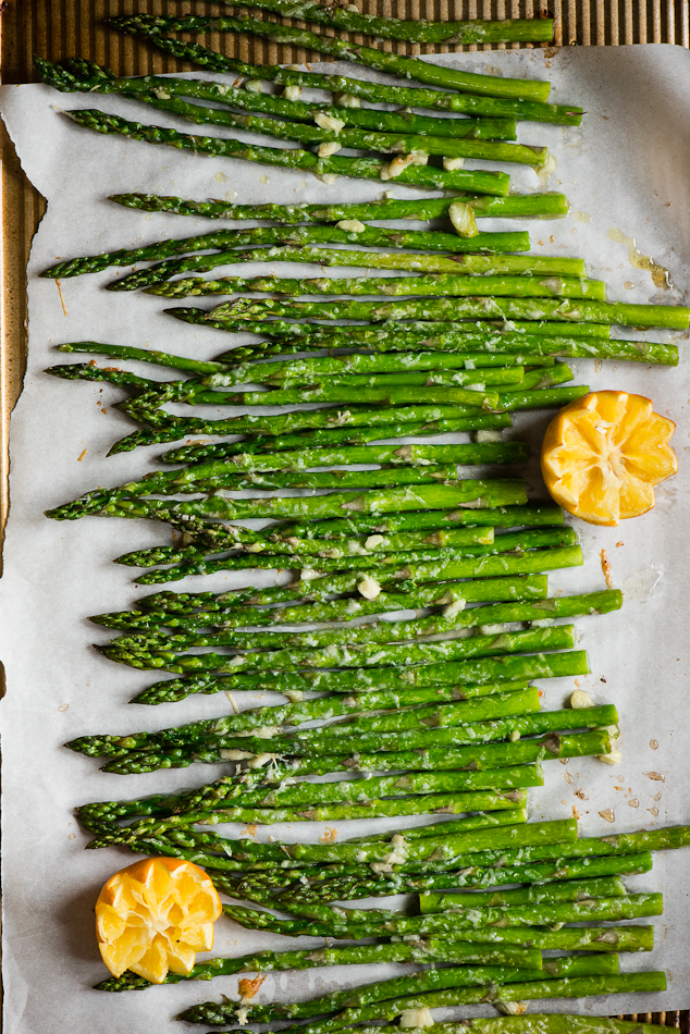 Oven Roasted Asparagus spread out on parchment paper garnished with oranges