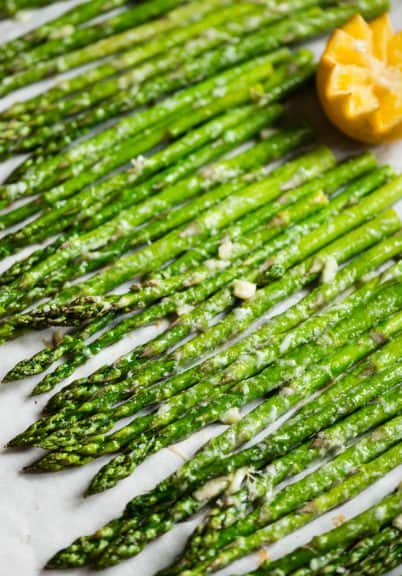 roasted asparagus lined up on parchment paper