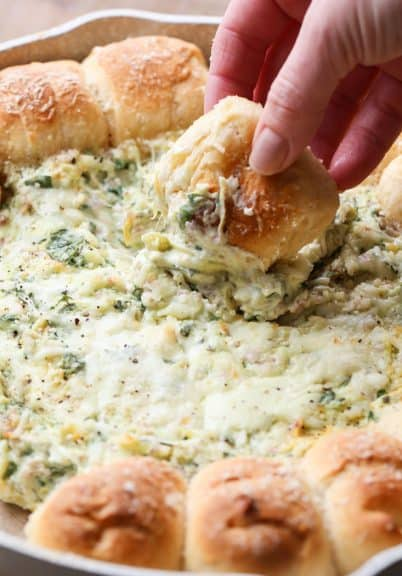 Pull-A-Part crescents with spinach artichoke dip in a skillet with a piece of bread being dipped into the spinach dip