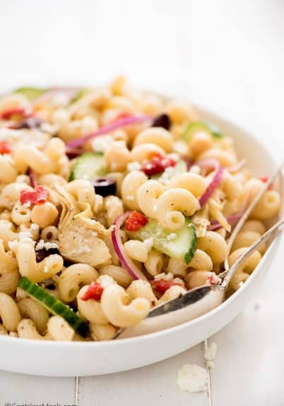 Mediterranean pasta salad in a white bowl with serving spoons