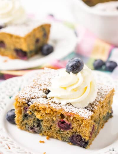 Overnight blueberry coffee cake on a plate with icing and a blueberry on top
