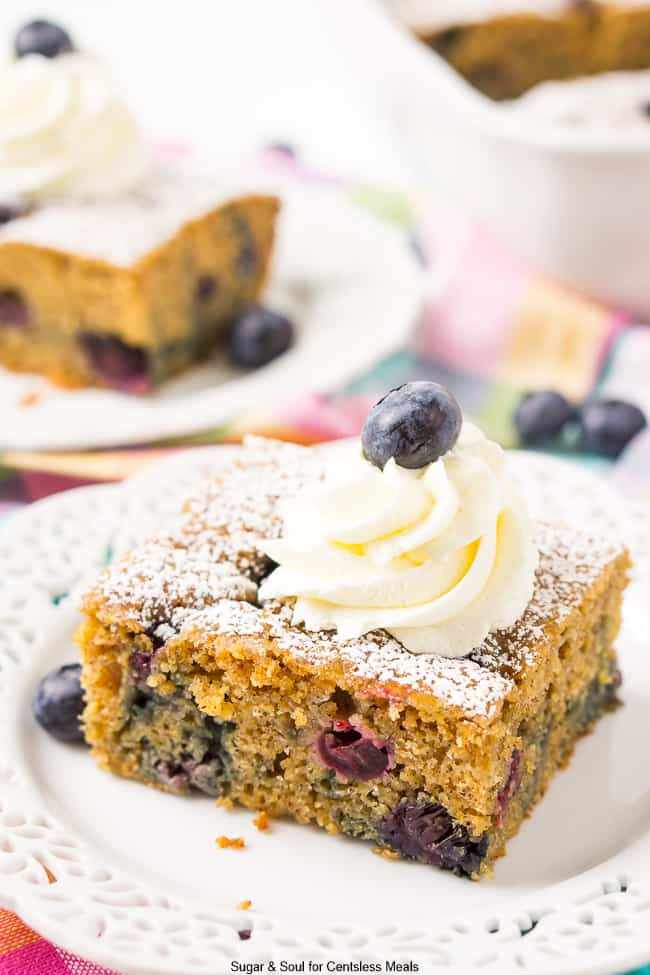 A slice of Overnight Breakfast Blueberry Cake on a white plate with lace trim