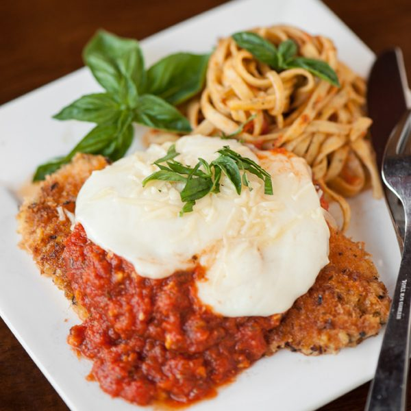 Chicken parmesan on a plate with basil and noodles
