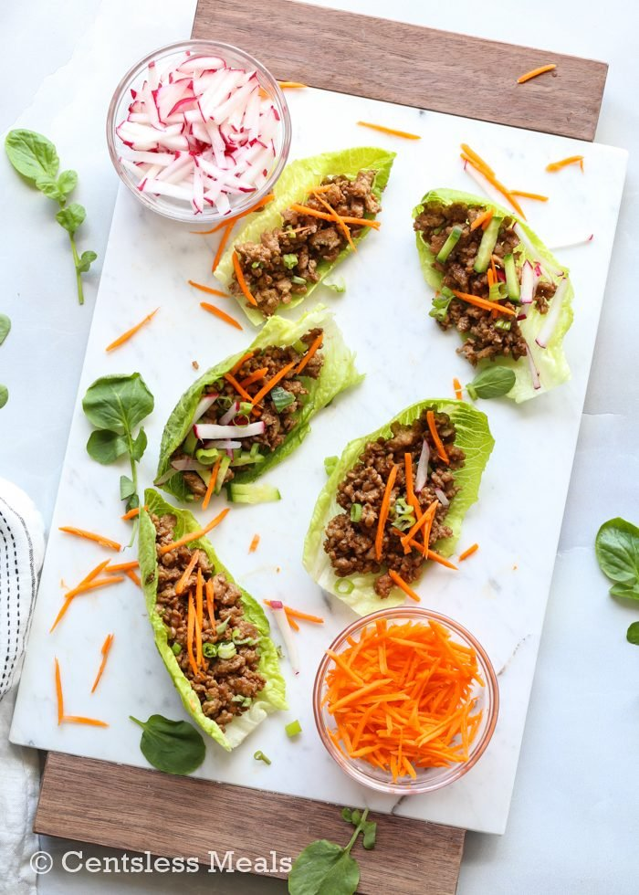 Lettuce wraps on a white platter with veggies for garnish.