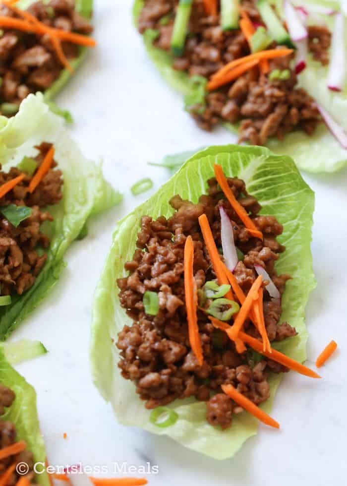Chicken Lettuce Wraps on a serving platter and garnished with carrot and radish