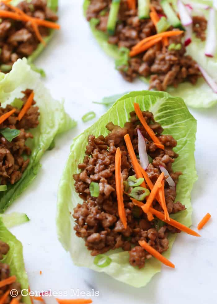 Chicken lettuce wraps with carrots green onions and radishes on top