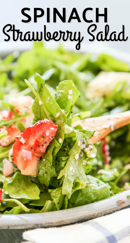 Spinach Strawberry Salad in a bowl and served with a wooden spoon