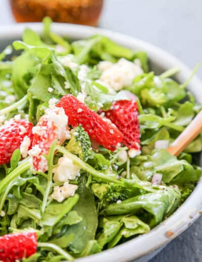 Spinach strawberry salad in a bowl topped with cheese