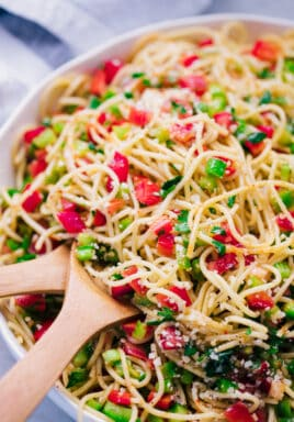 Spaghetti salad in a white bowl with wooden utensils