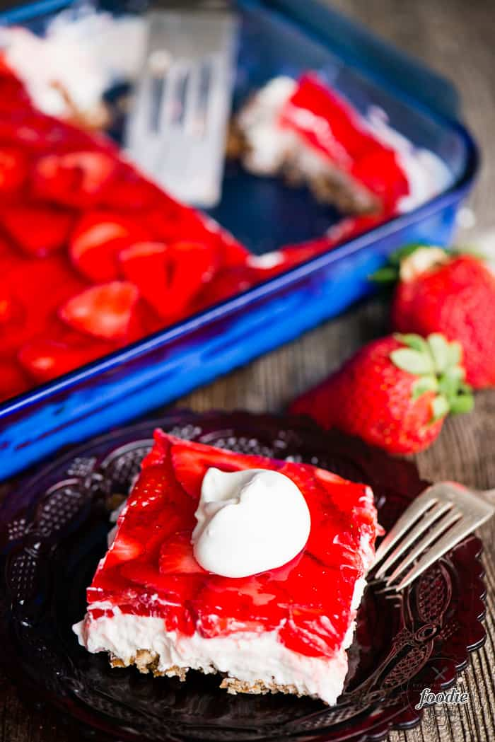 Strawbery Pretzel Salad in a dish and on a plate with whipped cream on top