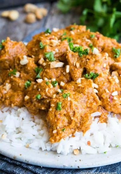 Butter chicken on a bed of white rice, garnished with cilantro and cashews