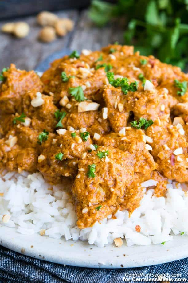 Butter chicken on a white plate with rice garnished with parsley and cashews