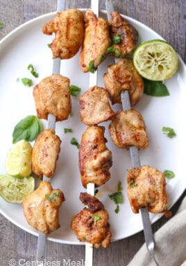 Lime grilled chicken kabobs on a white plate with cilantro and lime wedges