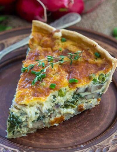 Spinach quiche on a plate garnished with thyme and green onions