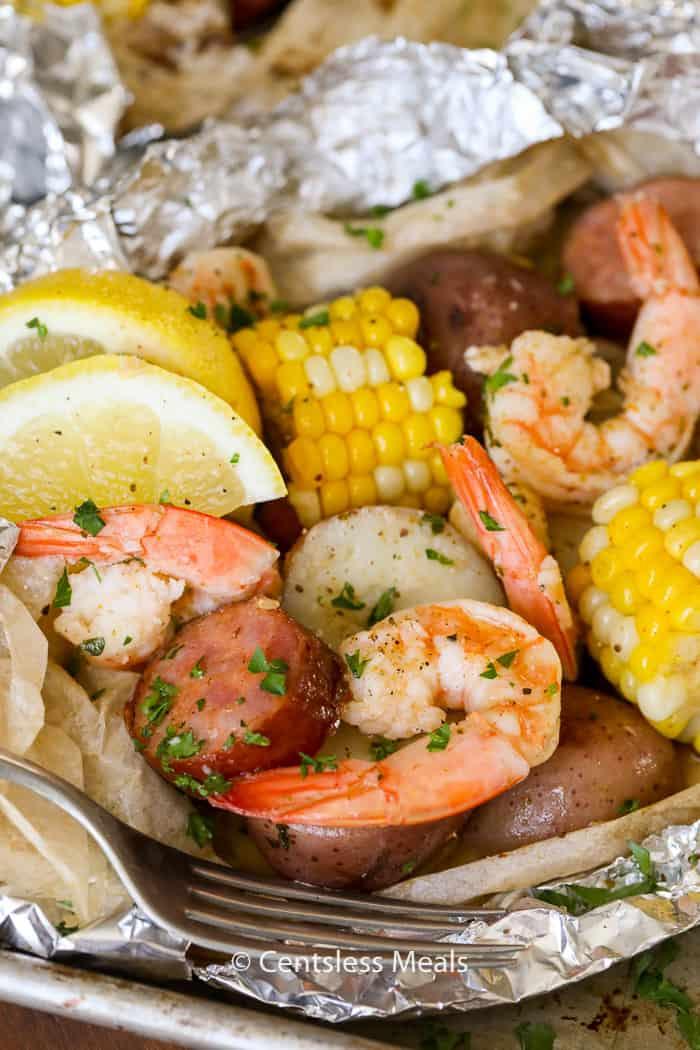 Shrimp boil foil packets with a fork and lemon slices