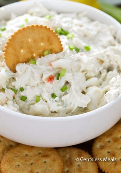 Crab dip in a white bowl garnished with green onions with a cracker
